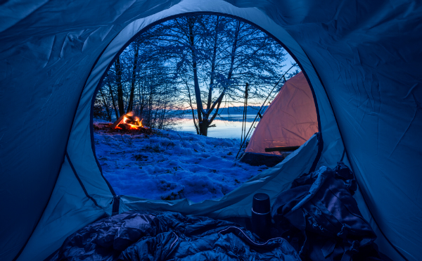 Winterliches Camping am See mit Lagerfeuer