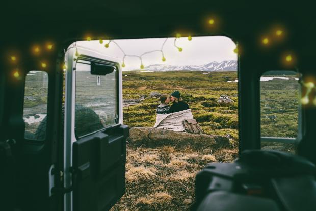 Ein verliebtes Pärchen kuschelt vor ihrem Wohnmobil in unberüherter Natur - der eingebaute Wechselrichter liefert Strom für die Glühbirnen, die im Wohnmobil leuchten