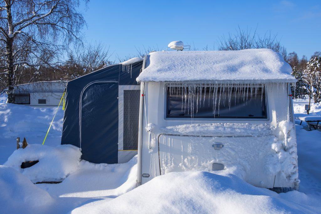 Tief eingeschneiter Wohnwagen. Manche Campingplätze haben für Dauercamper auch das ganze Jahr geöffnet.