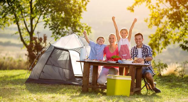 Fröhliche Familie mit 2 Kindern beim Campen - die ACSI Campingcard 2019 spart Geld