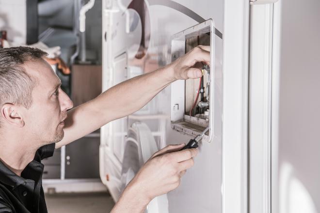 Mann arbeitet an Heizung im Wohnmobil