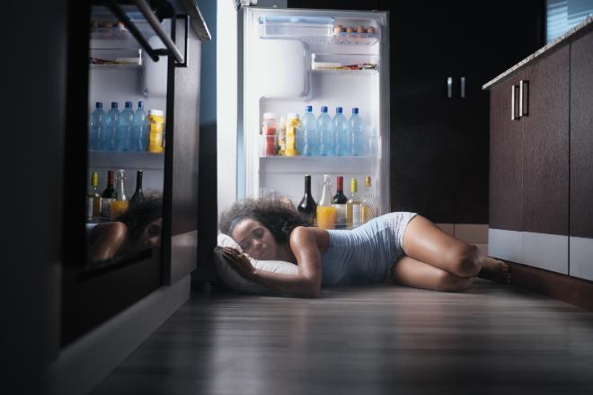 Frau schläft vor offenem Kühlschrank