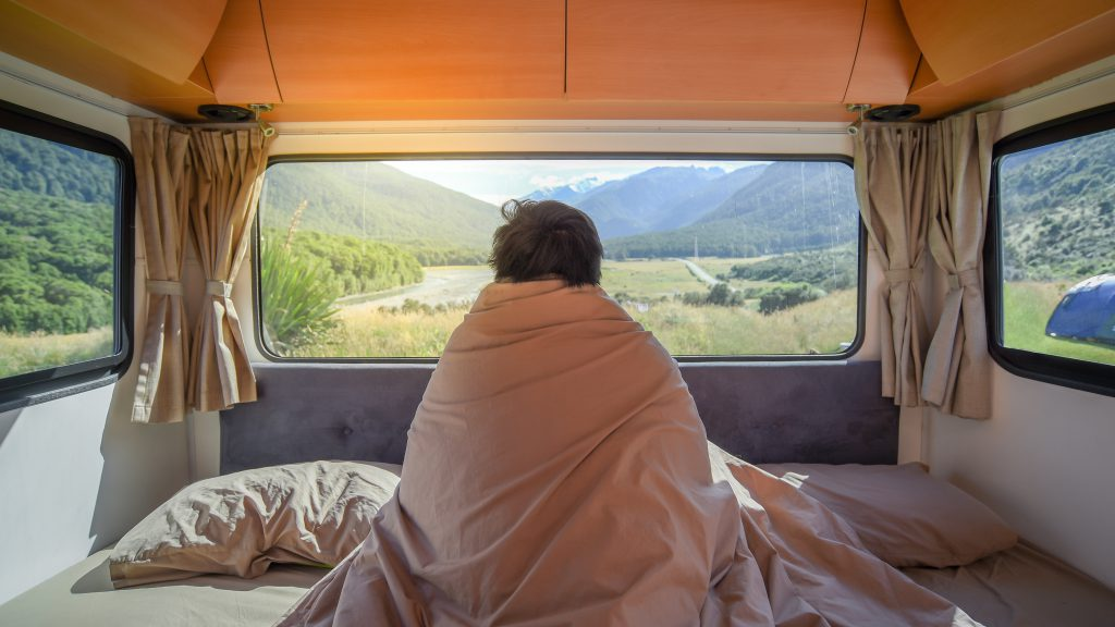 Eingehüllt in Decken geniesst ein Camper den Ausblick. Schlafkomfort ist beim Dauercaming wichtig. Achten Sie auf die Kissen und Decken, die der Witterung entsprechen.