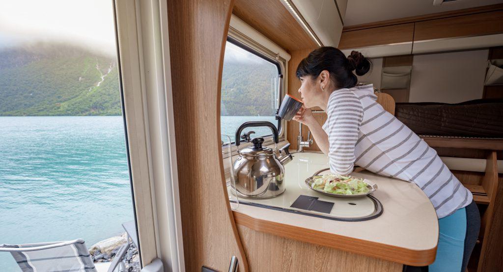 Eine Frau blickt aus dem Fenster ihres Wohnmobils auf einen See und trinkt aus einer Tasse - Der Alltag beim Dauercamping ist beschaulich und ruhig