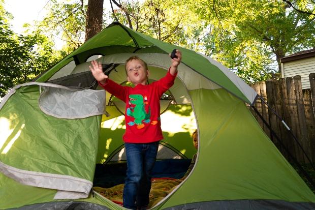Junge kommt aus Zelt im Garten