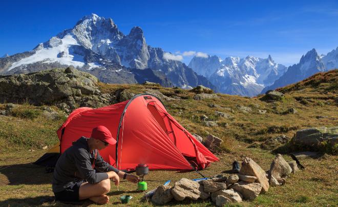 Mann im Zelt in den Alpen - autarkes Camping