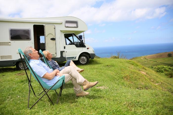 Aelteres Paar entspannt in Campingklappstuehlen