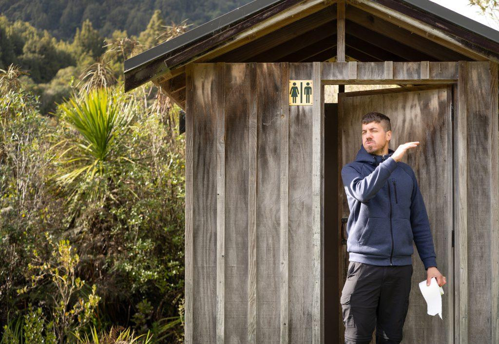 Ein Mann verlässt die Toilette eines Campingplatzes und macht dabei eine angeekelte Geste Thetford Campingklos und Eimertoiletten
