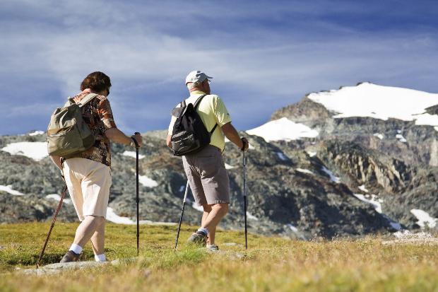 Ein älteres Paar, das mit Wanderstöcken und leichtem Gepäck auf einer Tageswanderung unterwegs ist. Hiking vs Trekking