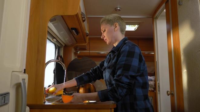 Frau benutzt Wasserhan im Wohnmobil