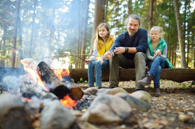 Vater mit 2 Töchtern am Grillplatz im Wald - Camping im Oktober