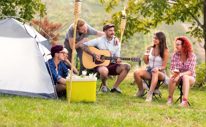Gruppe junger Leute beim Camping - Isolierboxen sorgen für kühle Getränke