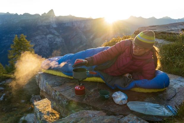 Junge Frau liegt morgens draussen in einem Schlafsack - Biwakieren im Freien