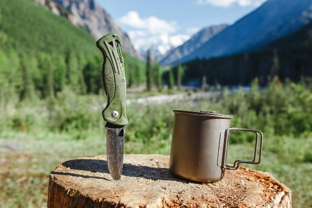 Messer und Becher vor bergigem Hintergrund - Equipment zum Biwakieren