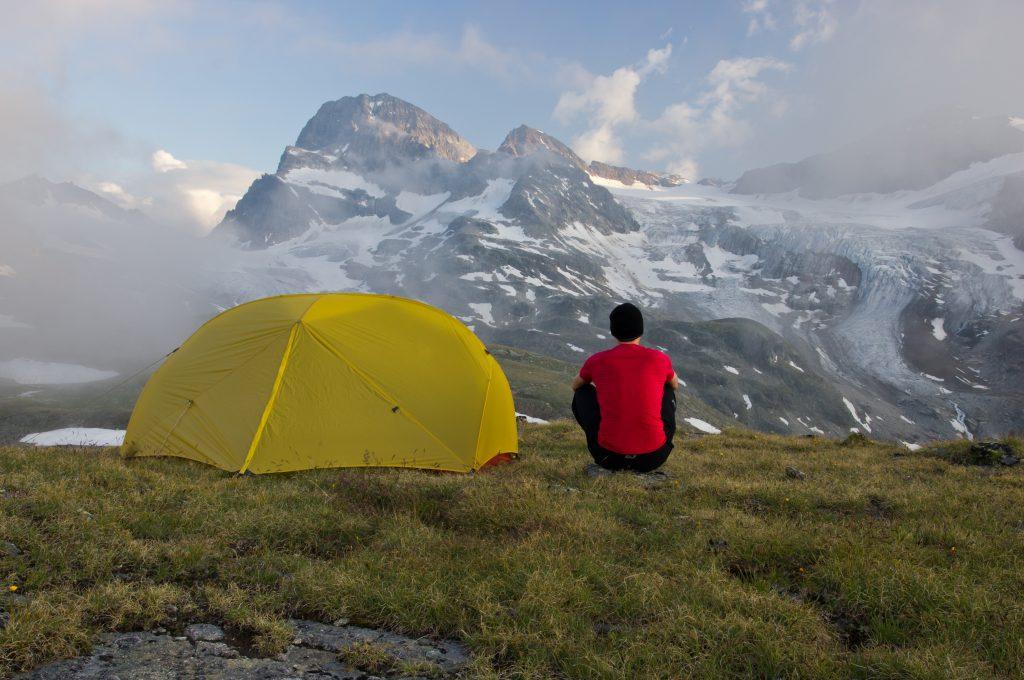Camper mit Zelt sitzt am Berghang - Biwakieren in den Alpen