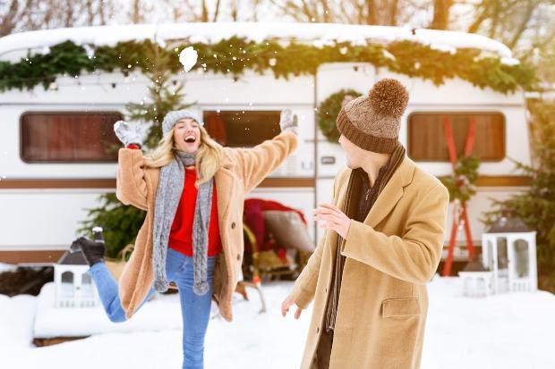 Junges Paar macht Schneeballschlacht , im Hintergrund ein Camper-Van - Ganzjahrescamping