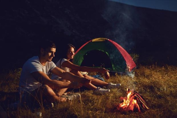 Junge Paar campt und sitzt am Lagerfeuer