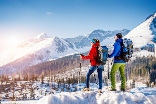 Zwei Wanderer beim Winterwandern in bergiger Schneelandschaft