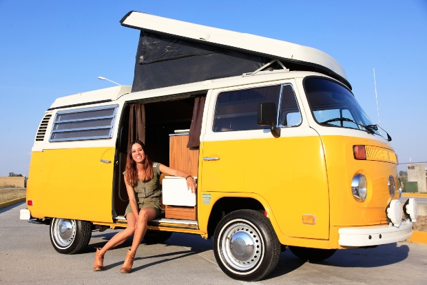 Junge Frau sitzt in einem gelben VW Bulli, Faltdach