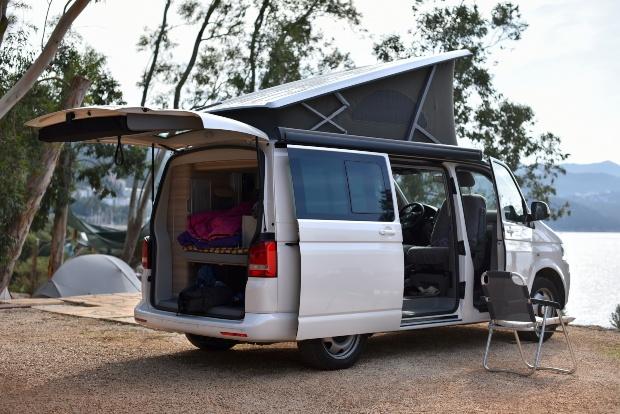 Camping Van steht nahe eines Sees, Faltdach ist hochgeklappt