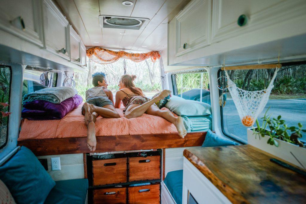 Zwei junge Damen liegen im selbst ausgebauten Camper
