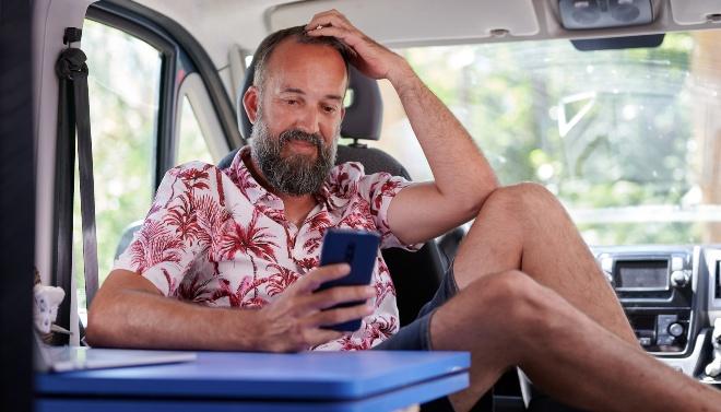 Mann schaut im Camper sitzend auf sein Handy