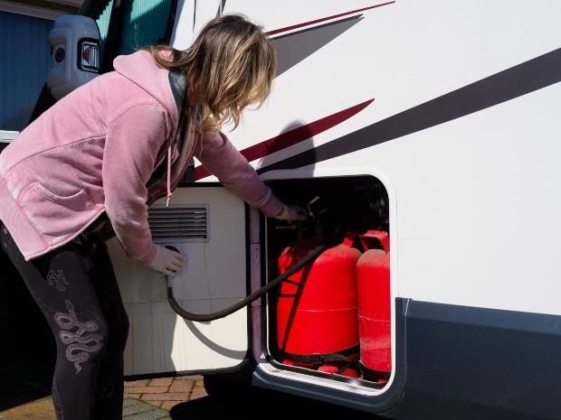 Frau prüft Gasflaschen am Wohnmobil - Gasleitung im Wohnwagen prüfen