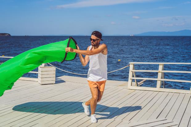 Mann am Wasser bläst ein Luftsofa auf