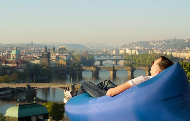 Mann im Luftsessel mit traumhaftem Ausblick auf eine Stadt